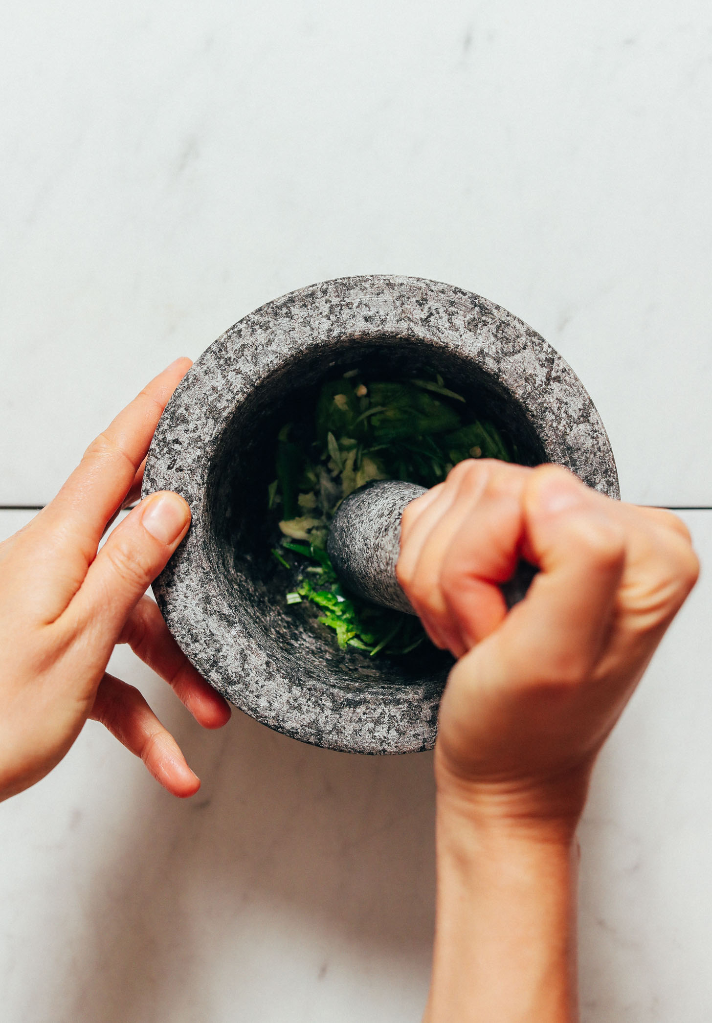 Using a mortar and pestle to crush serrano and garlic for our Rosemary Guacamole recipe