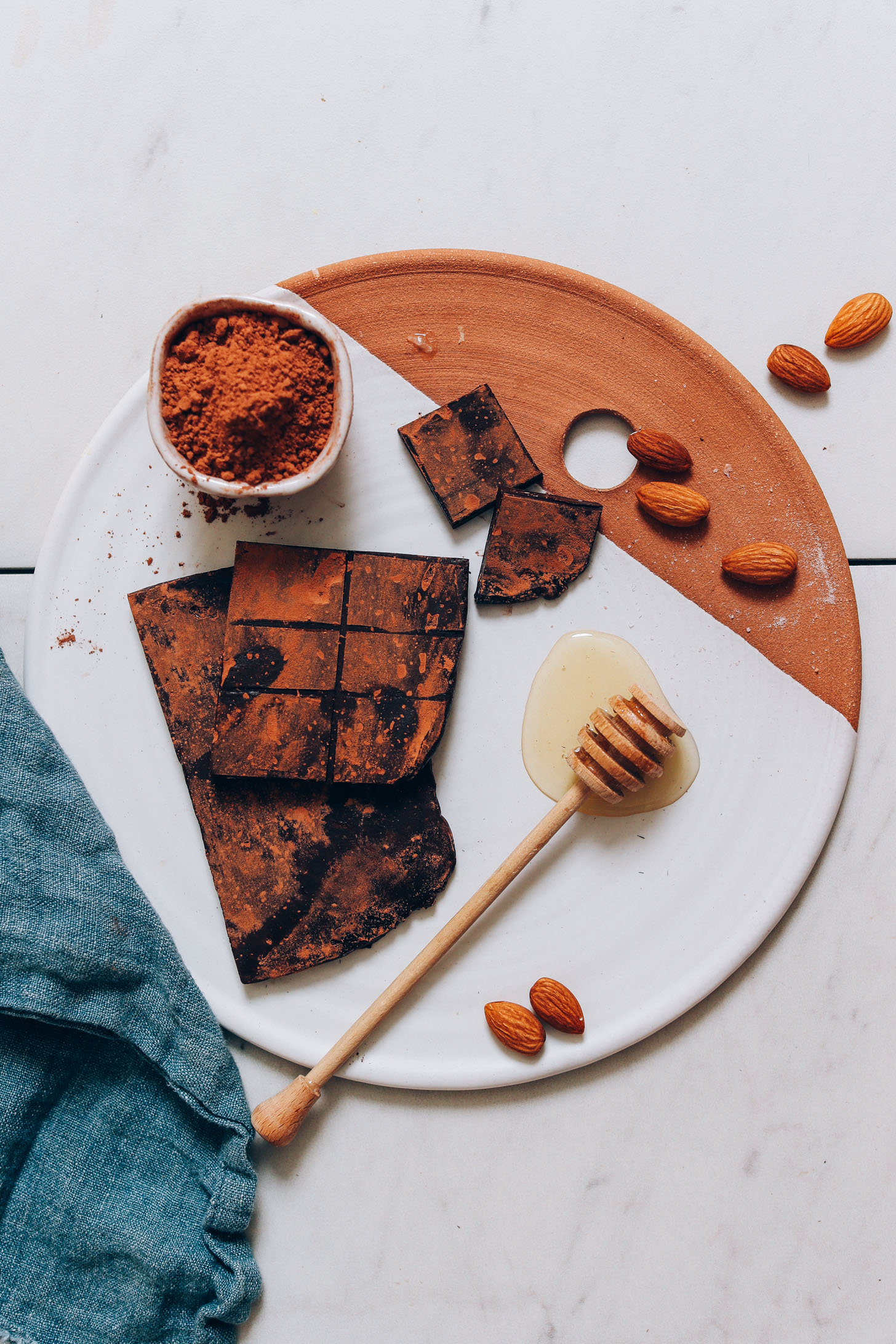 Ceramic and clay tray with almonds, cacao powder, and homemade Honey Mama's Bars
