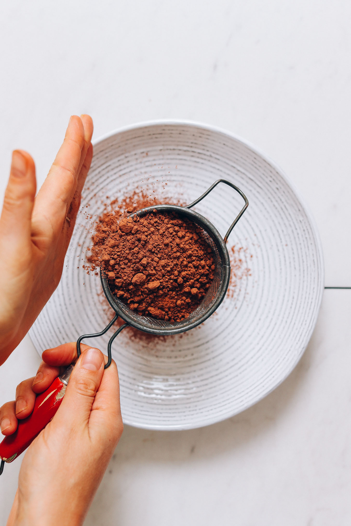 Using a fine mesh strainer to sift cacao powder into a bowl