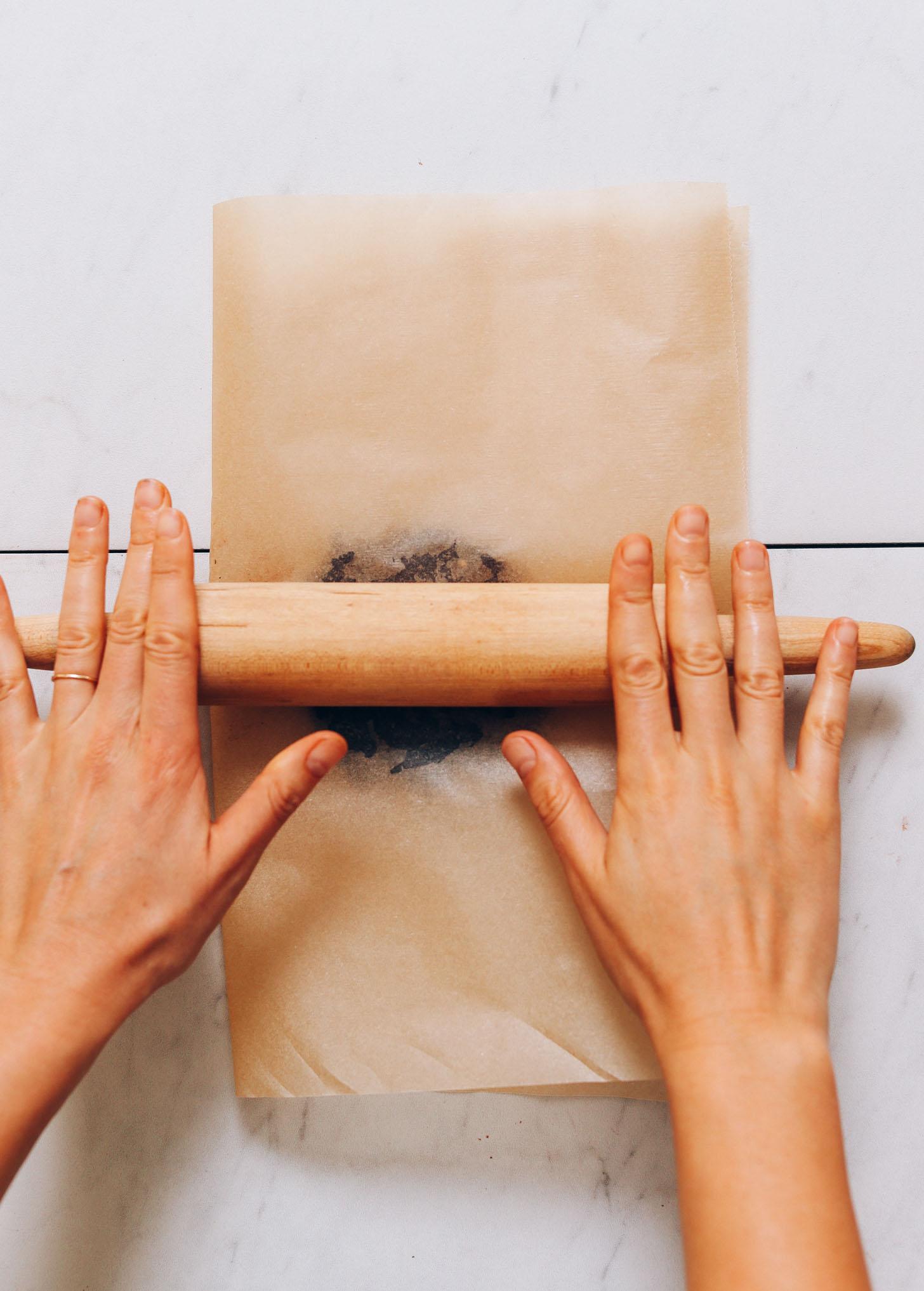 Usando un rodillo sobre papel pergamino para enrollar chocolate endulzado con miel en barras