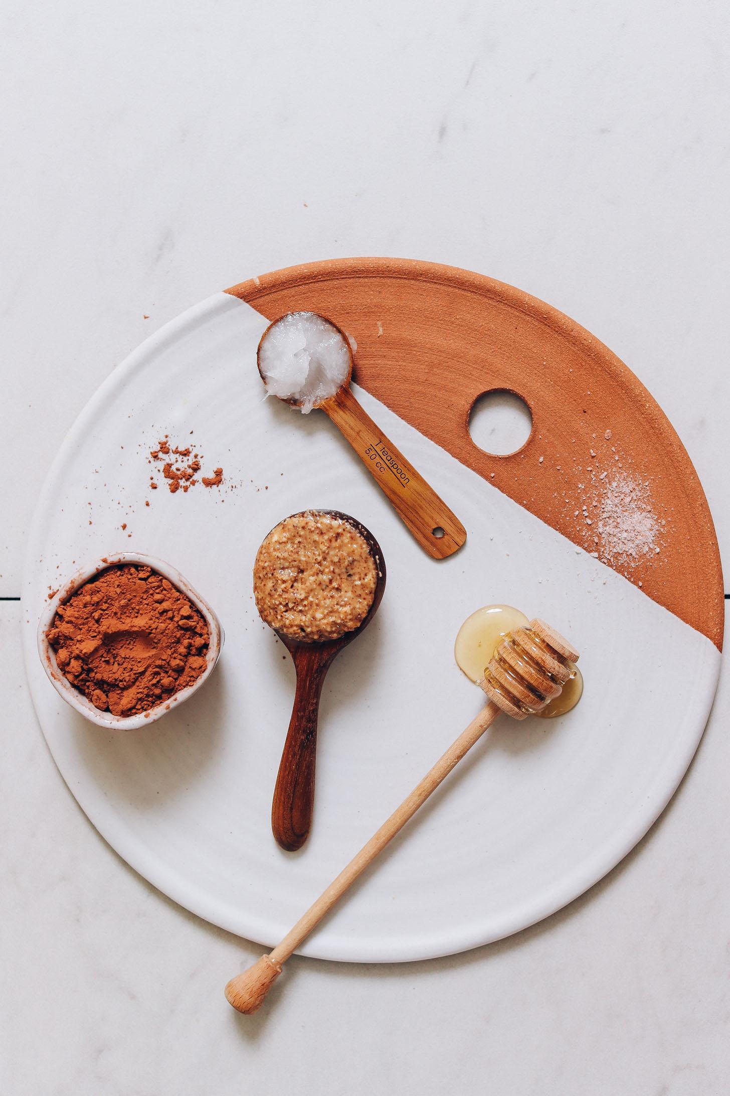 Bandeja de arcilla y cerámica con miel, mantequilla de almendras, sal, aceite de coco y cacao en polvo.