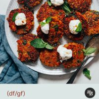 Plate of Crispy Quinoa Sweet Potato Fritters topped with dairy-free yogurt