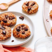 Spoonful of sea salt next to four of our no bake chocolate chip cookies