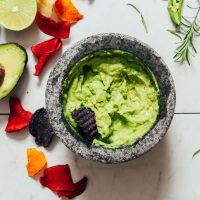 Mortar and pestle of Serrano & Rosemary Guacamole with veggie chips