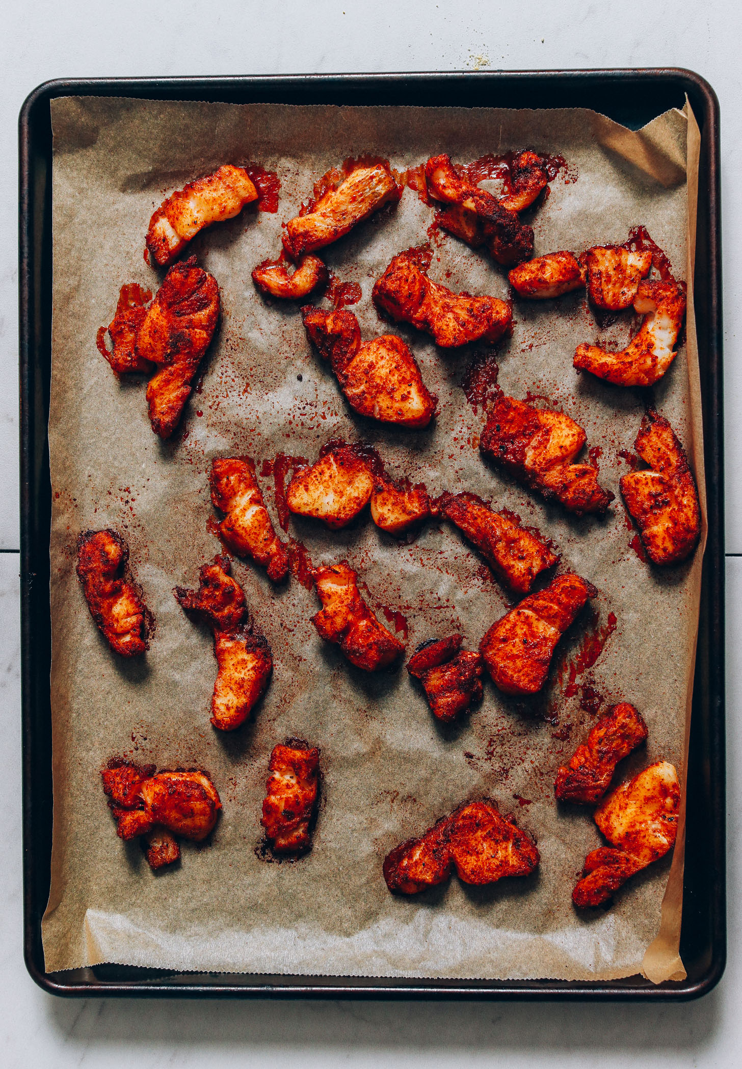 Parchment-lined baking sheet with freshly baked cod coated in spices for making Fish Tacos