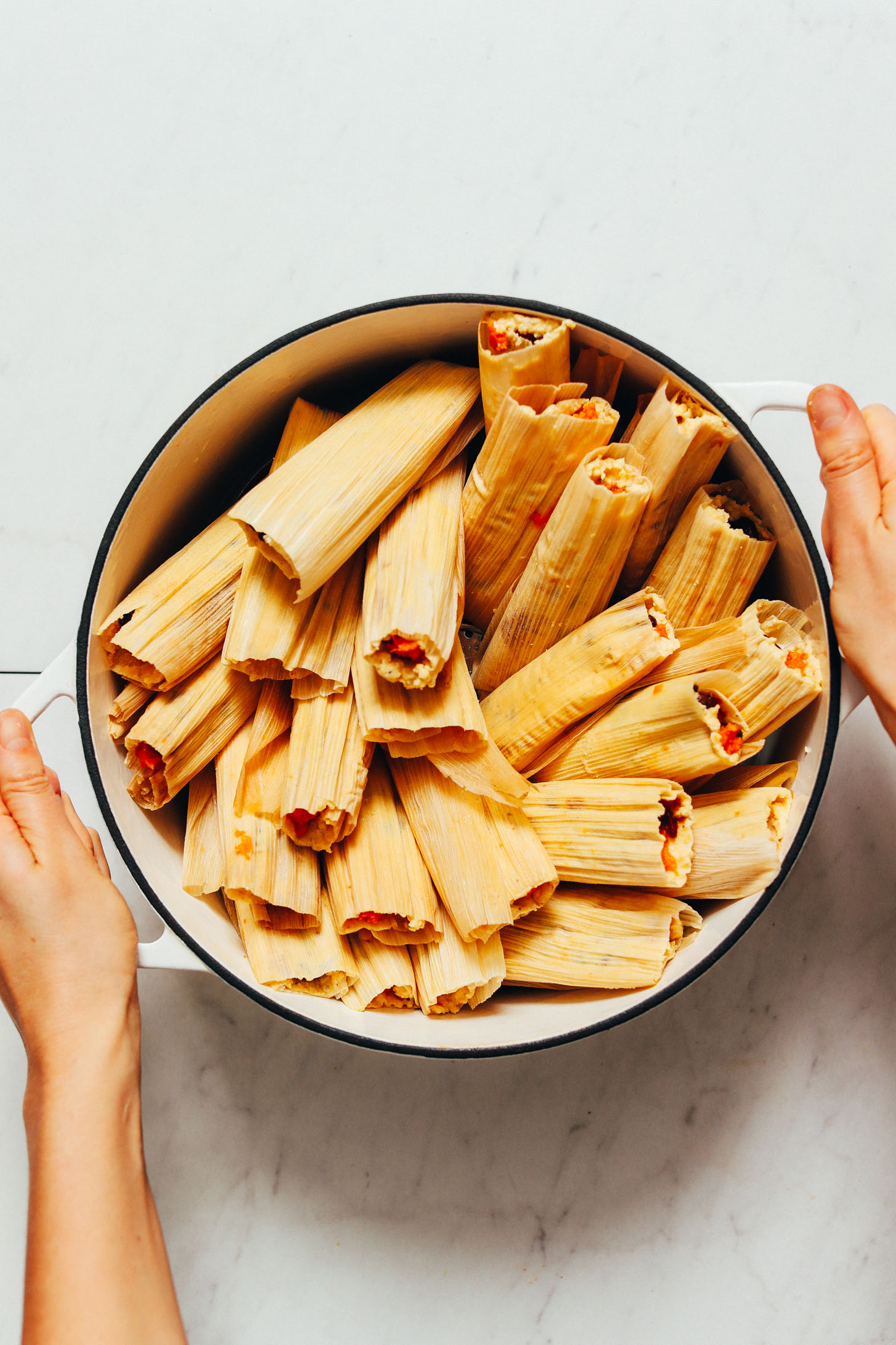 Holding a pot of homemade tamales for our tutorial on How to Make Tamales