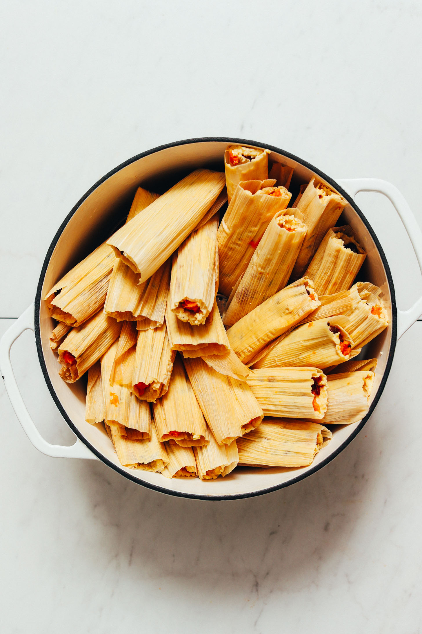 Large white pot filled with sweet potato black bean tamales