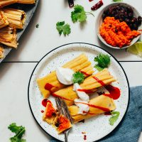 Plate of sweet potato black bean tamales topped with vegan sour cream and sriracha