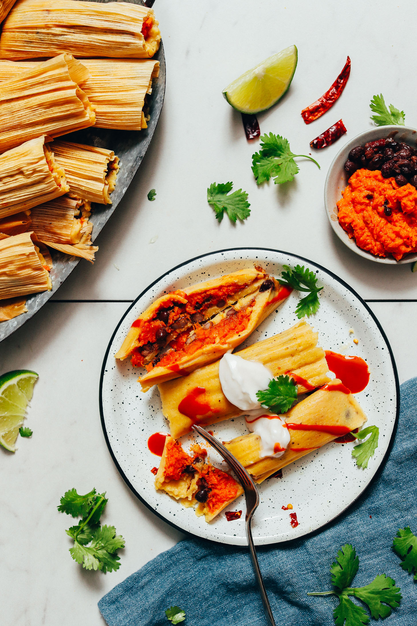 Using a fork to slice into a plate of vegan tamales