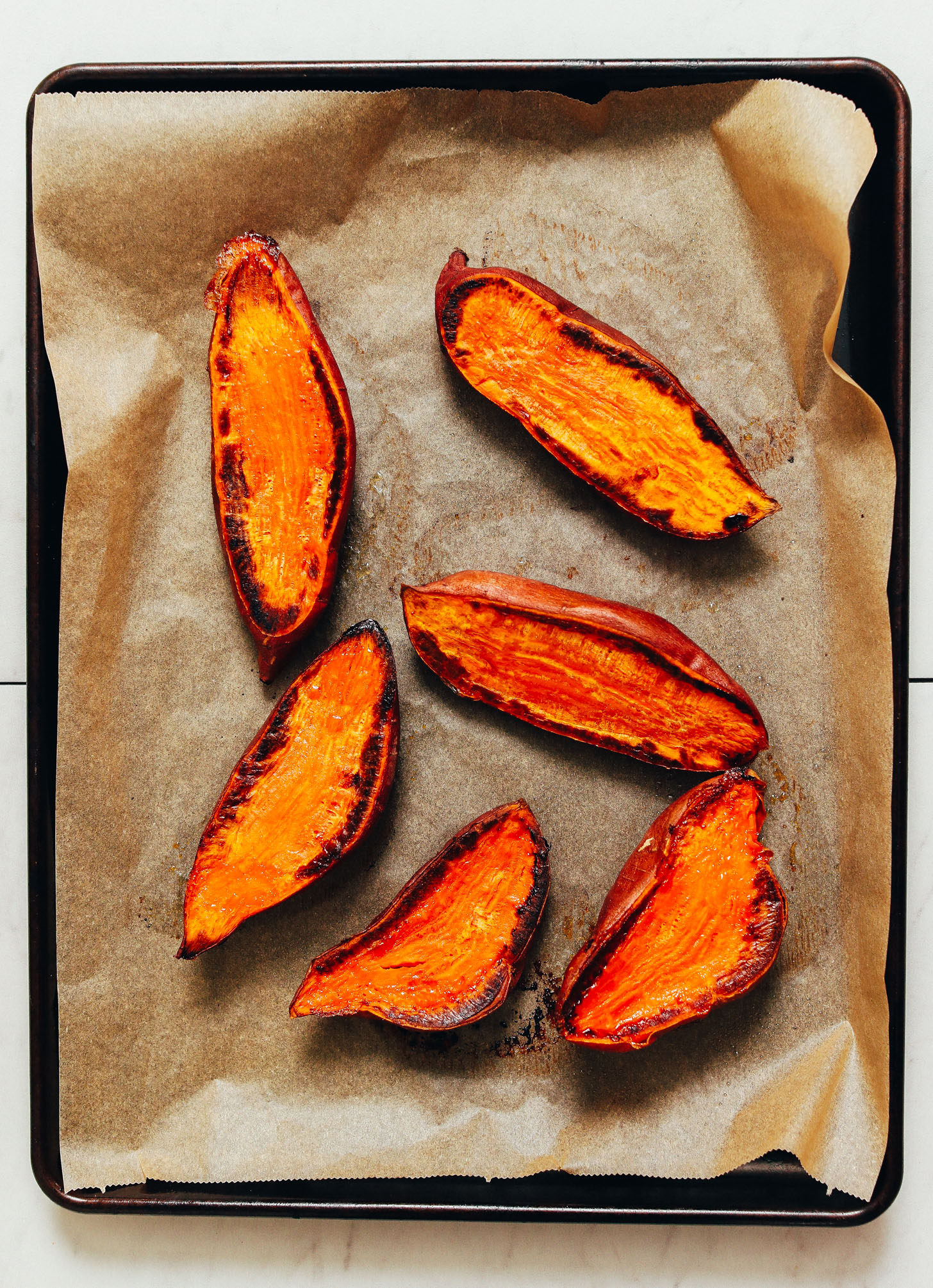 Parchment-lined baking sheet of halved and roasted sweet potatoes