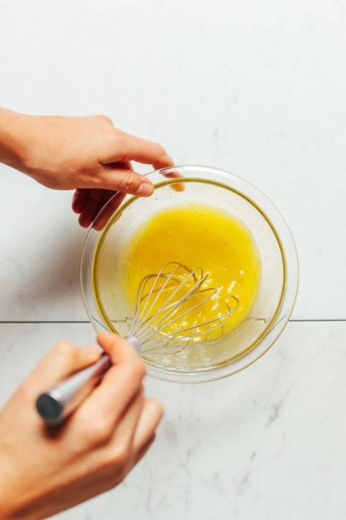 Whisking dressing ingredients in a small bowl to make homemade Lemon Vinaigrette