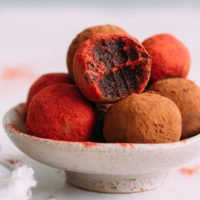 Bowl of No Bake Red Velvet Cake Balls coated in cacao powder and beet root powder