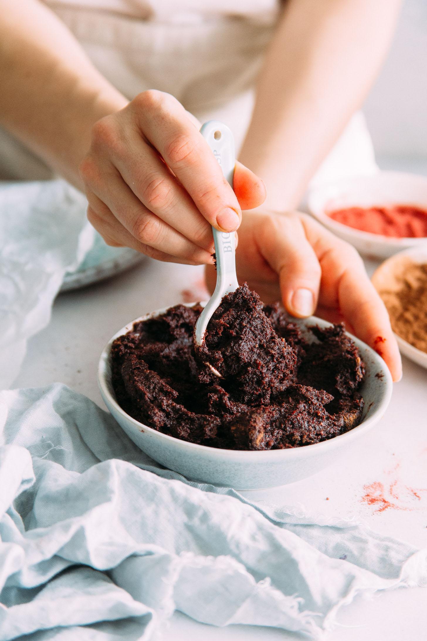 Colher em uma tigela de não assar bolo de veludo vermelho morde massa