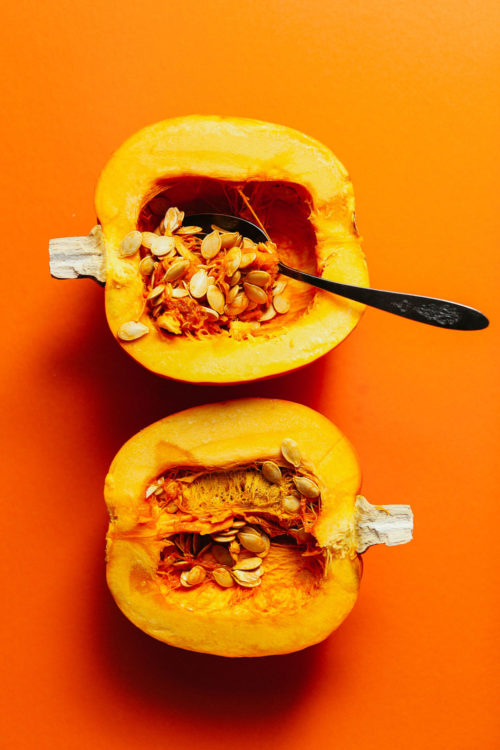 Halved pie pumpkin with a spoon scooping out the flesh and seeds to make Roasted Pumpkin Seeds