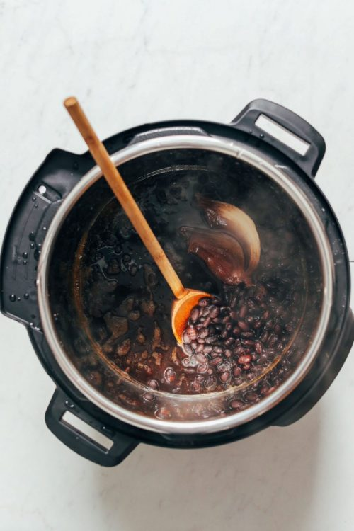 Wooden spoon in a pot of freshly cooked Instant Pot Black Beans