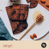 Honey whisk next to dark chocolate bars with cacao powder coating
