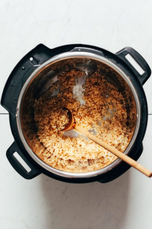 Wooden spoon in an instant pot with brown rice and water