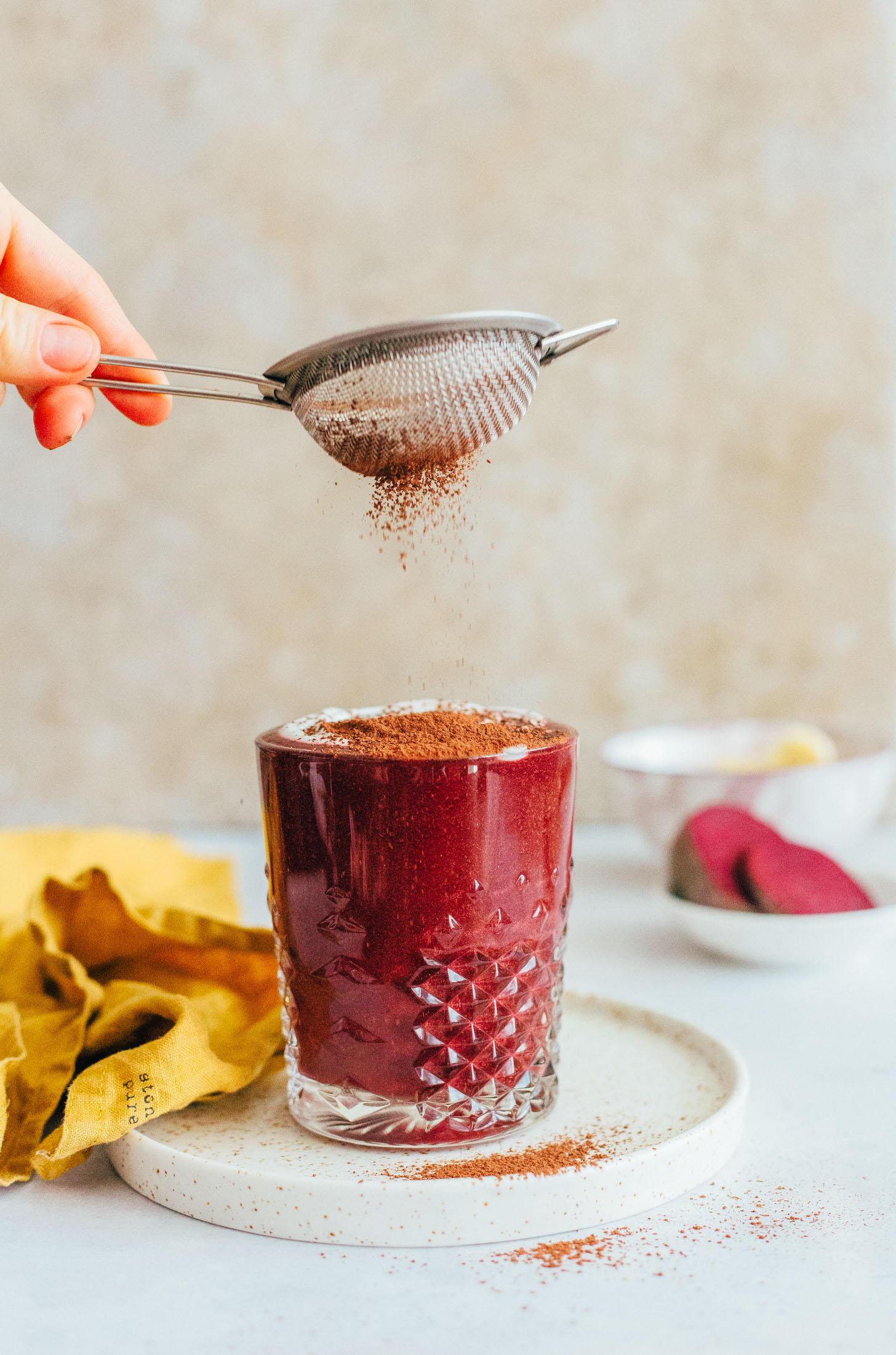 Sprinkling cacao powder over a glass filled with our beet smoothie recipe