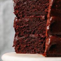 Triple layer Gluten-Free Vegan Chocolate Cake on a cake stand