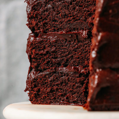 Triple layer Gluten-Free Vegan Chocolate Cake on a cake stand