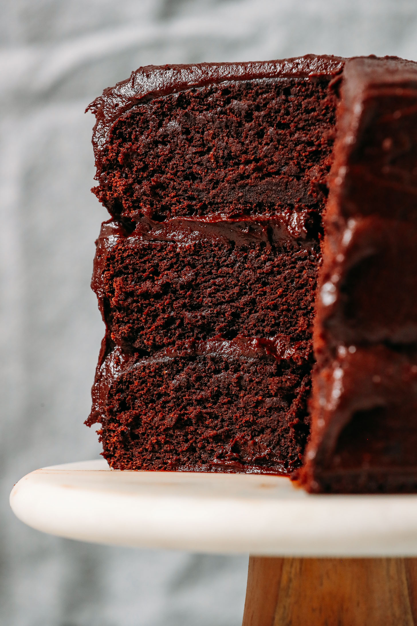 Close up shot of a slice of three layer Gluten Free Chocolate Cake with Vegan Chocolate Frosting