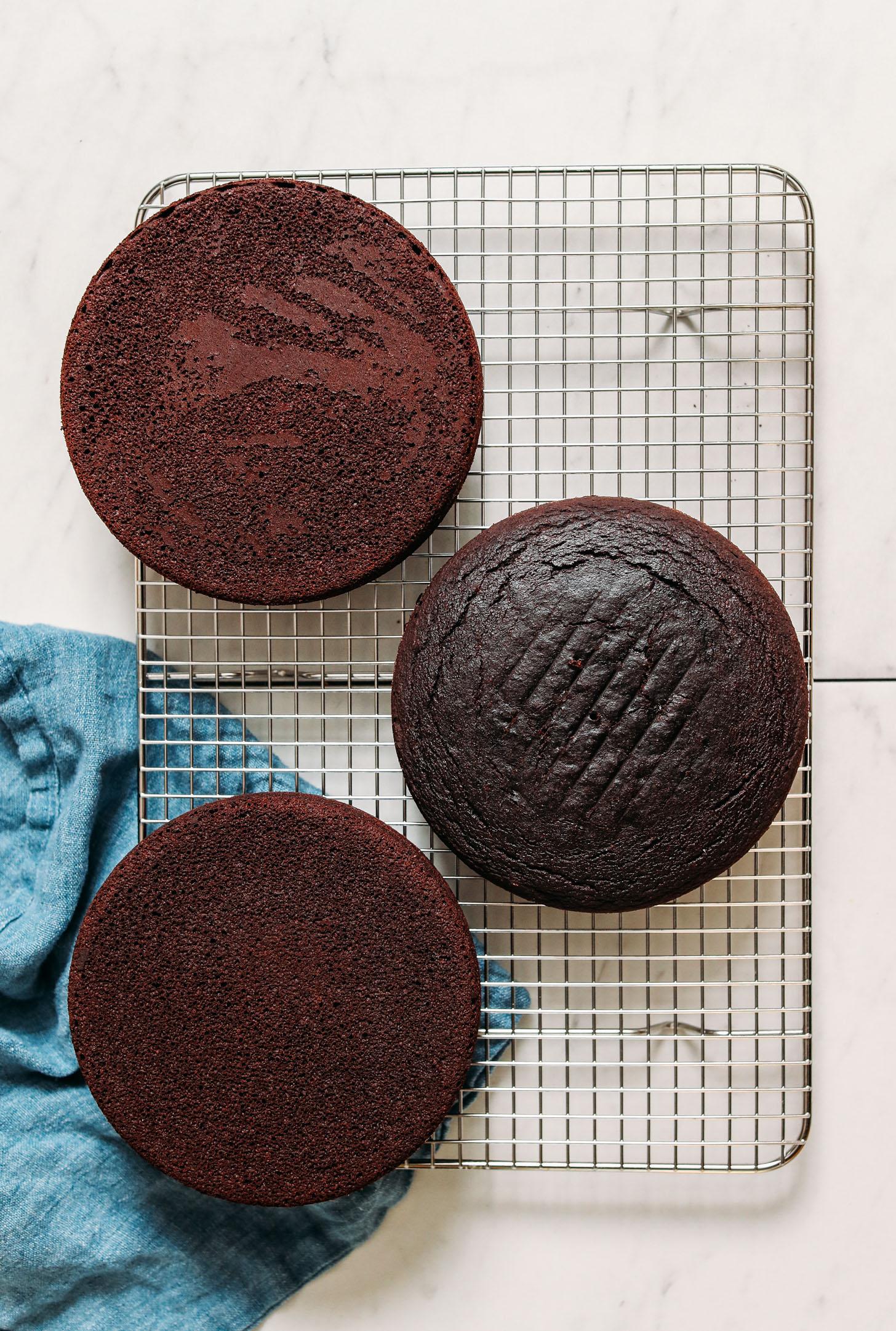 Tres rondas de pastel de chocolate vegano sin gluten en una rejilla para enfriar