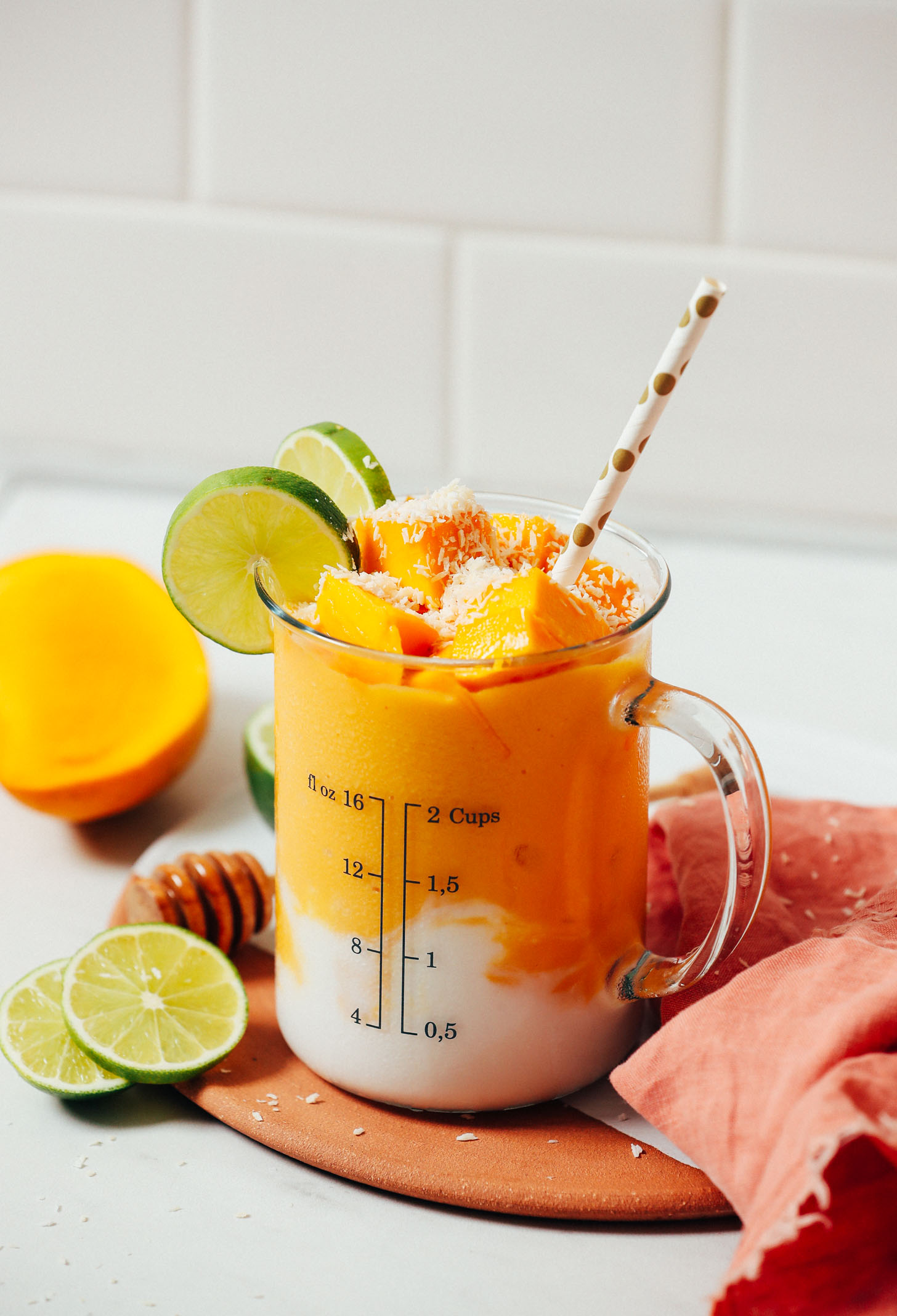 Coconut milk swirled at the bottom of a glass filled with our dairy-free Mango Lassi recipe