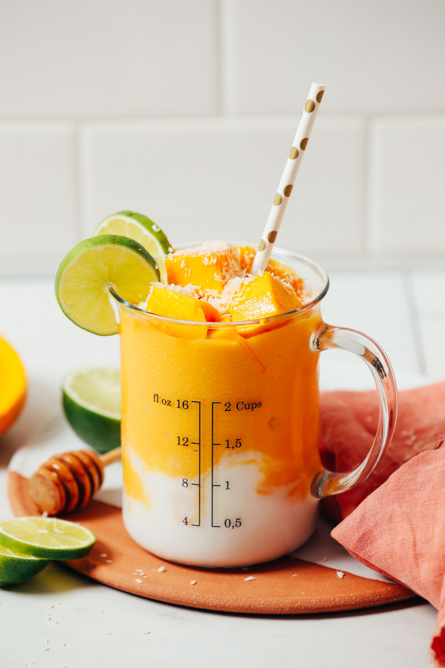 Measuring glass of our Mango Lassi Smoothie topped with coconut, mango chunks, and lime