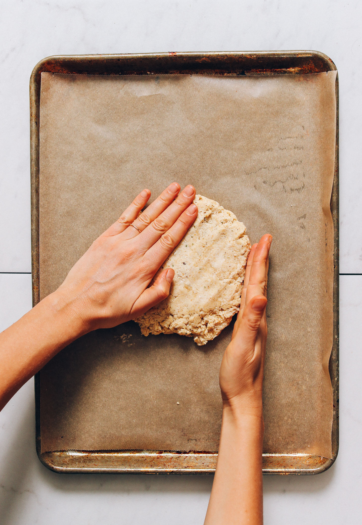 Shaping vegan gluten-free pizza dough on a baking sheet