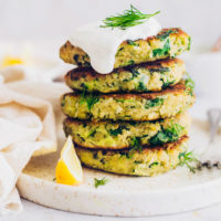 Stack of vegan zucchini fritters topped with coconut yogurt and dill