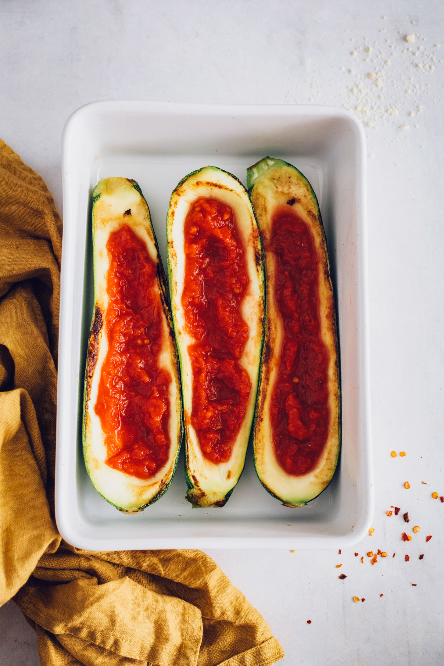 Baking pan of zucchini boats with marinara