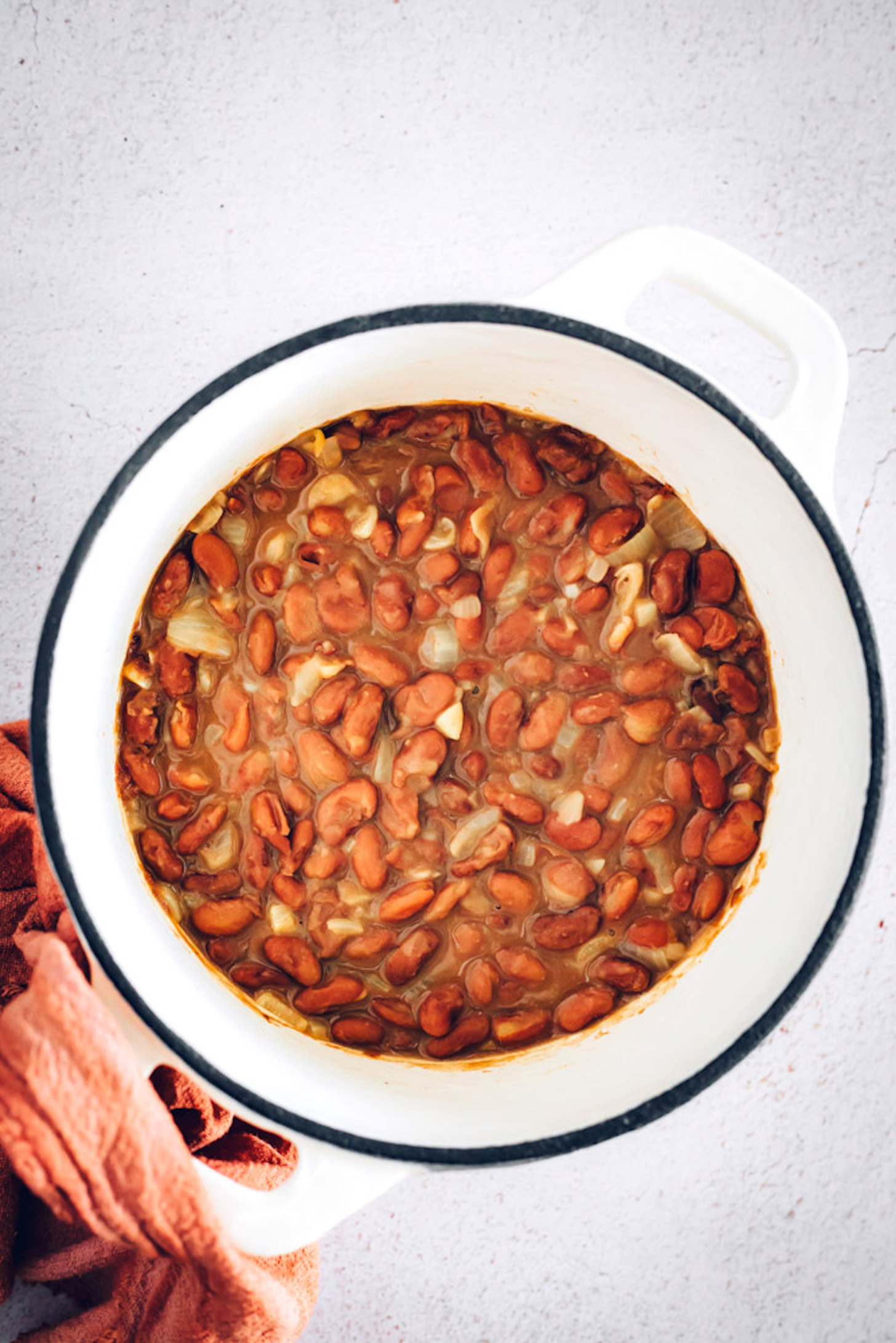 Dutch oven of cooked pinto beans seasoned with onion and garlic