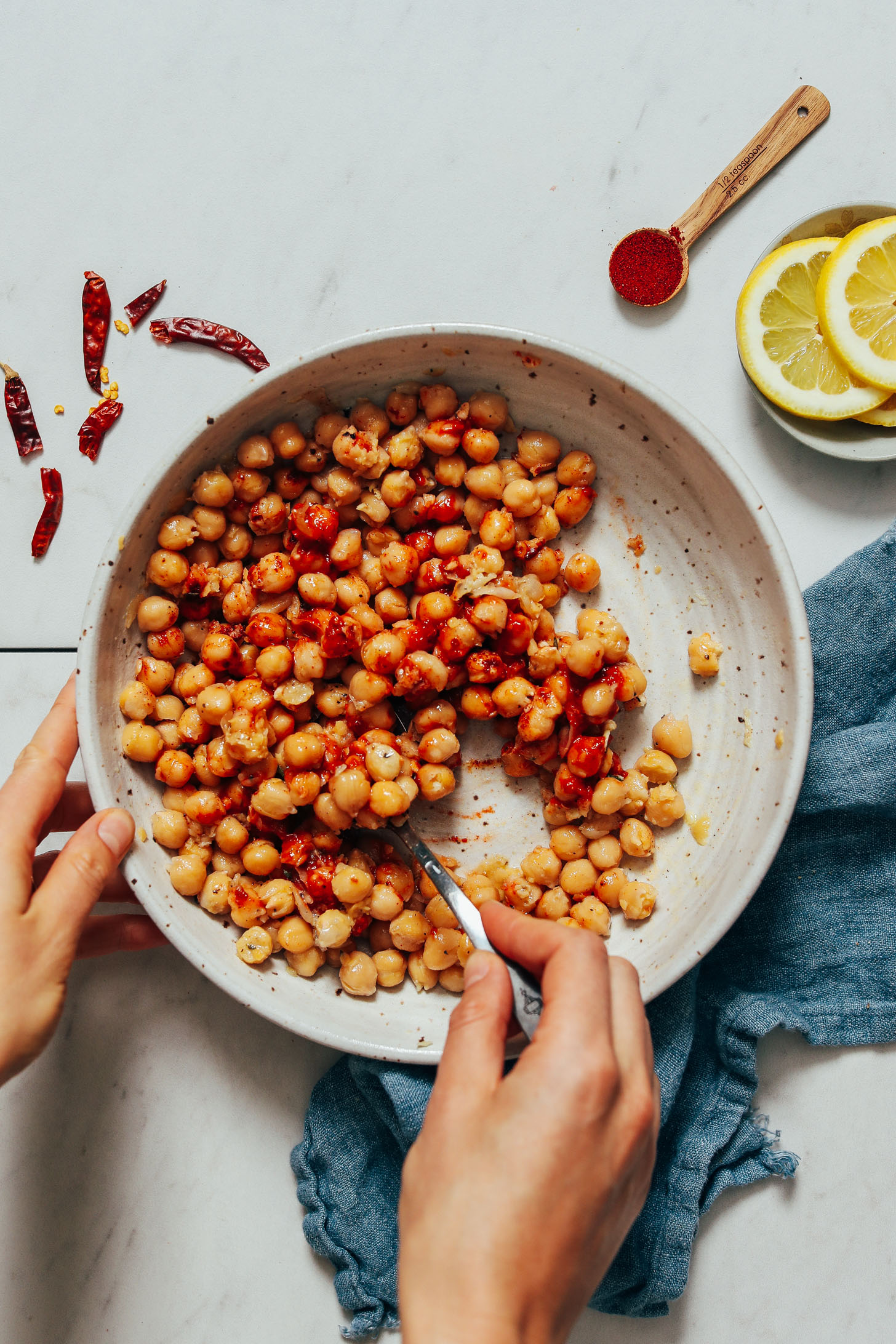 Using a spoon to stir together chickpeas, harissa paste, lemon juice, garlic, sea salt, maple syrup, smoked paprika, and olive oil