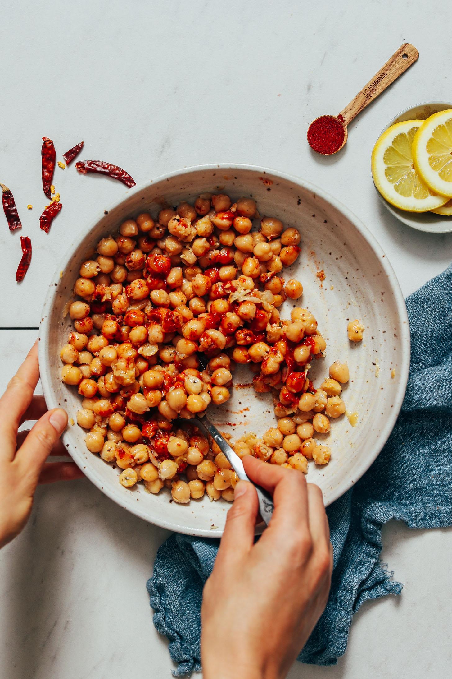 Usando una cuchara para mezclar los garbanzos, la pasta de harissa, el jugo de limón, el ajo, la sal marina, el jarabe de arce, el pimentón ahumado y el aceite de oliva.