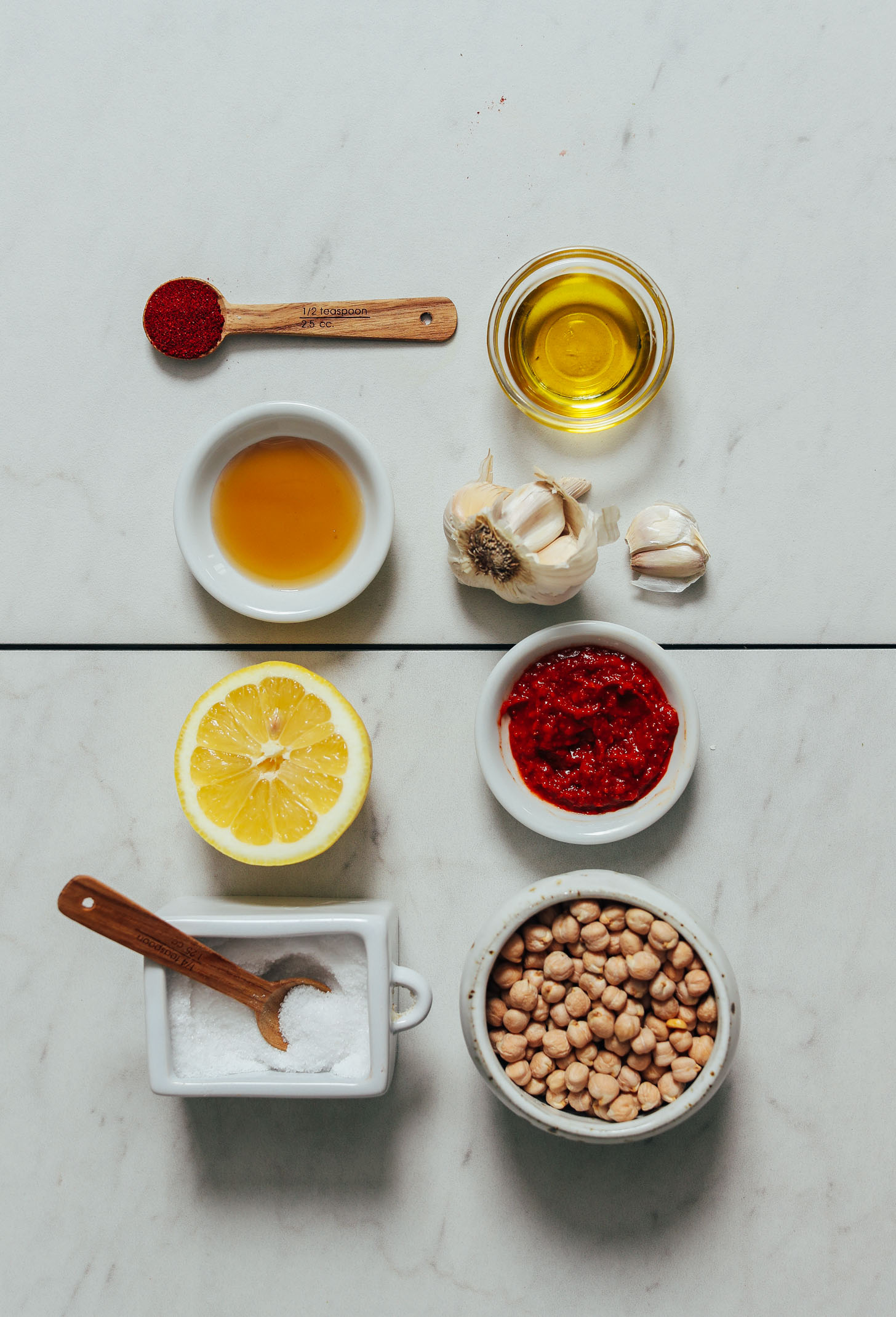 Spoons and dishes or salt, lemon juice, maple syrup, paprika, olive oil, garlic, harissa paste, and dry chickpeas