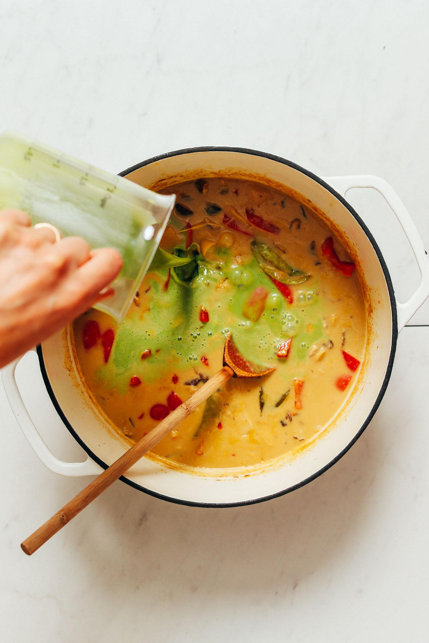 Verser de la poudre d'herbe d'orge dans un pot pour obtenir une couleur de curry vert plus vibrante