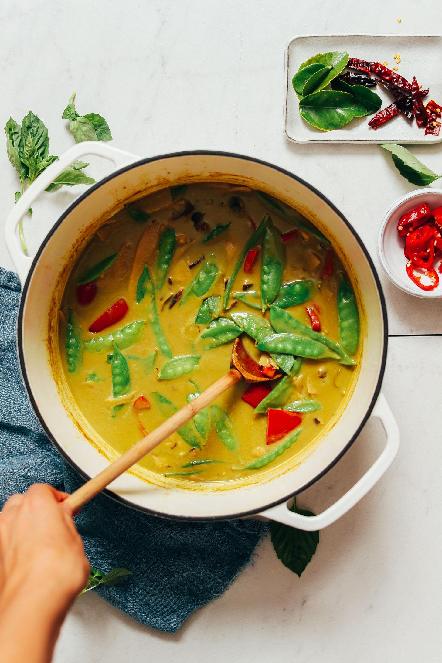 Piments, feuilles de lime kaffir et basilic à côté d'un pot de curry vert