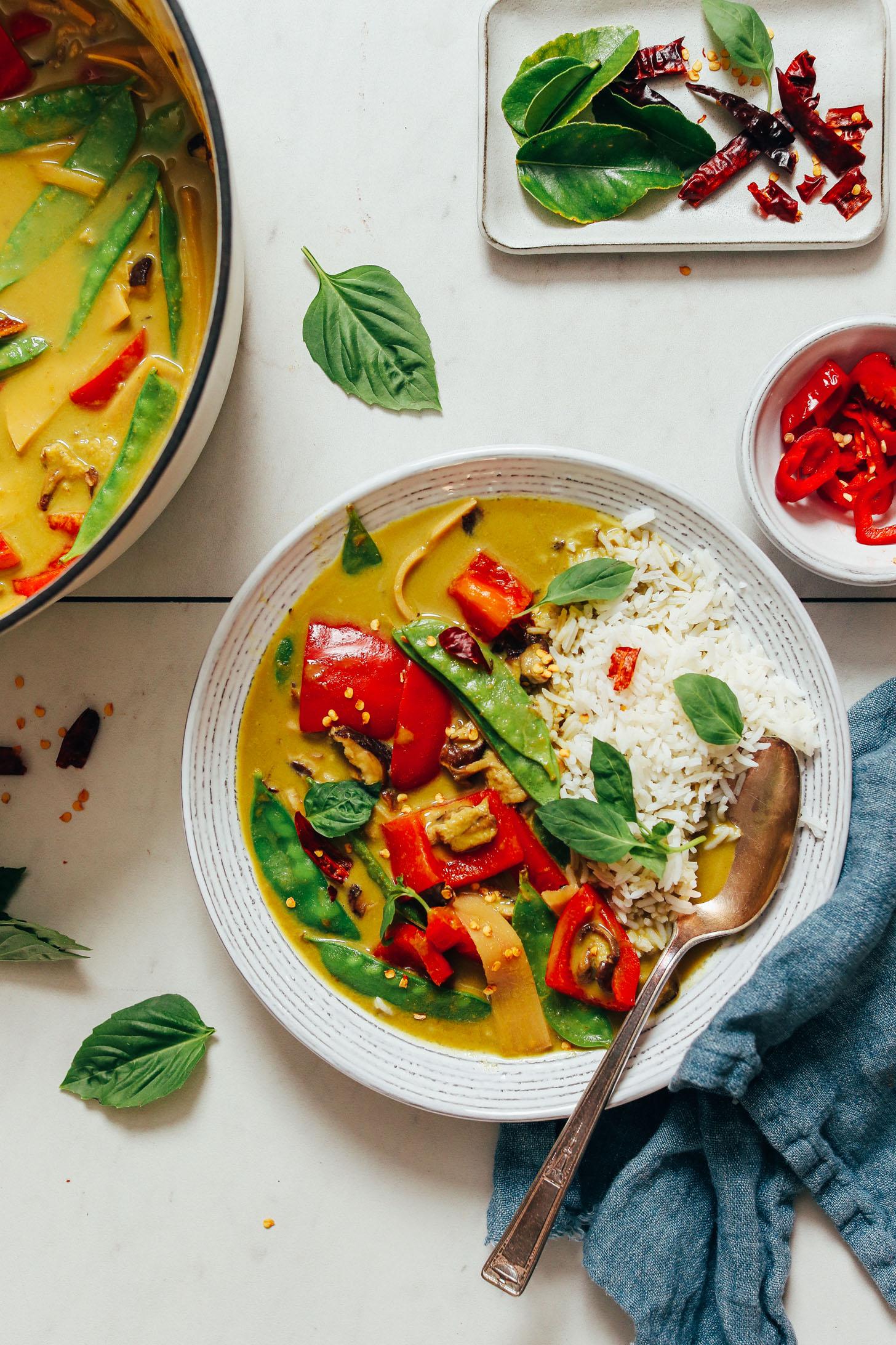 Bol de riz blanc et curry vert thaï à côté d'un pot de curry plus et ingrédients utilisés pour le faire