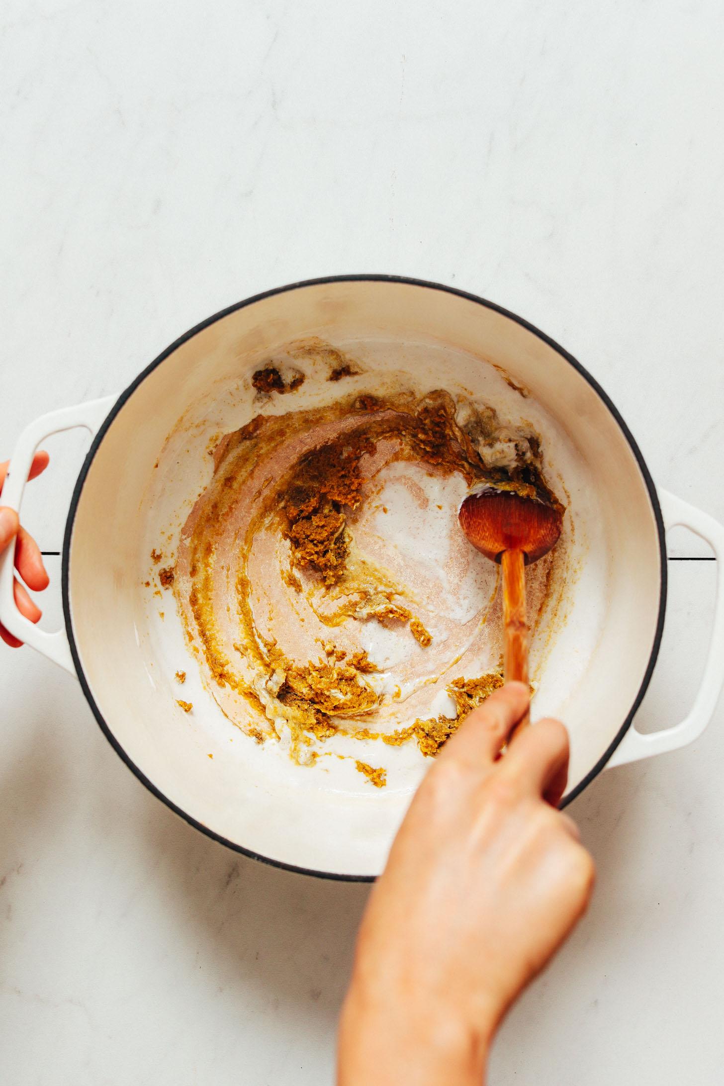 Remuer le lait de coco et la pâte de curry vert dans une casserole comme une astuce sans huile