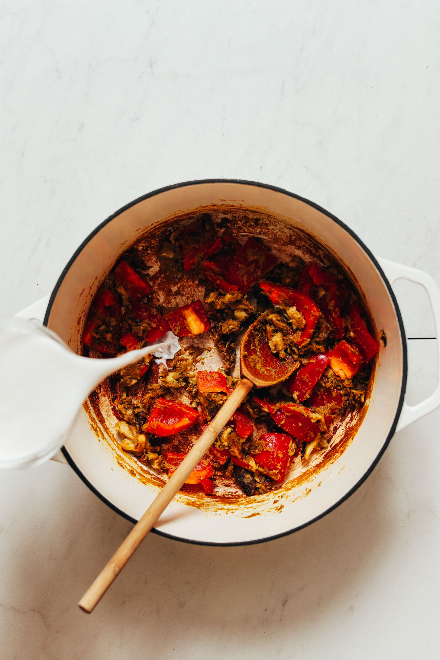 Verser le lait de coco dans une casserole de poivrons, de champignons et de pâte de curry vert