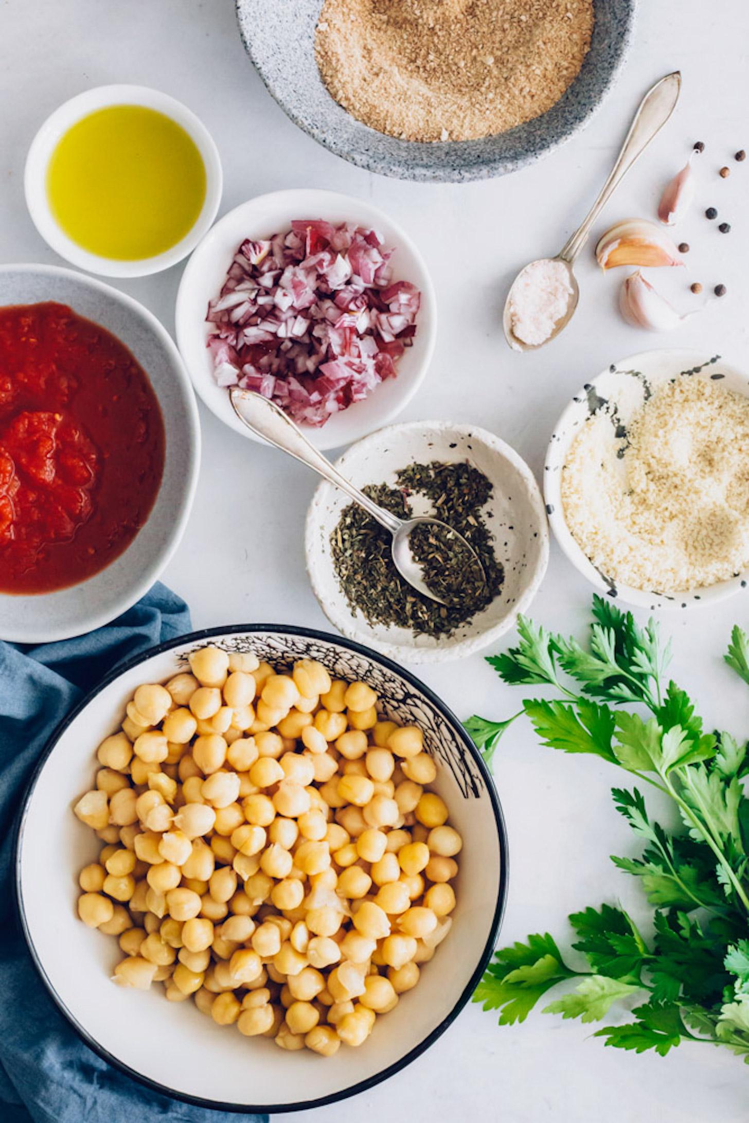 Tazones de garbanzos, condimentos italianos, cebolla roja, parmesano vegano, pan rallado, sal y aceite de oliva.
