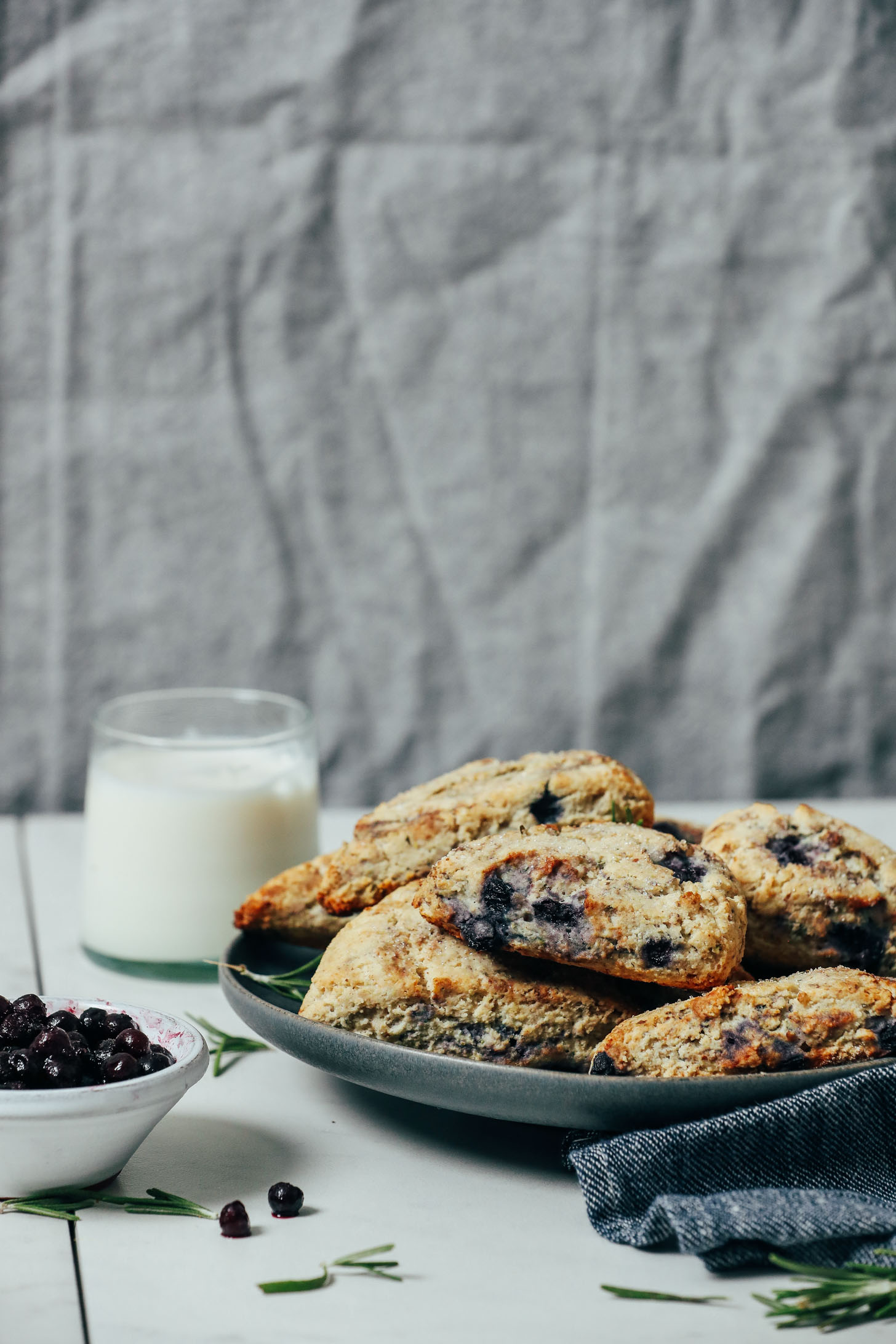 Wild blueberries, rosemary, and almond milk next to a large plate of Gluten Free Scones