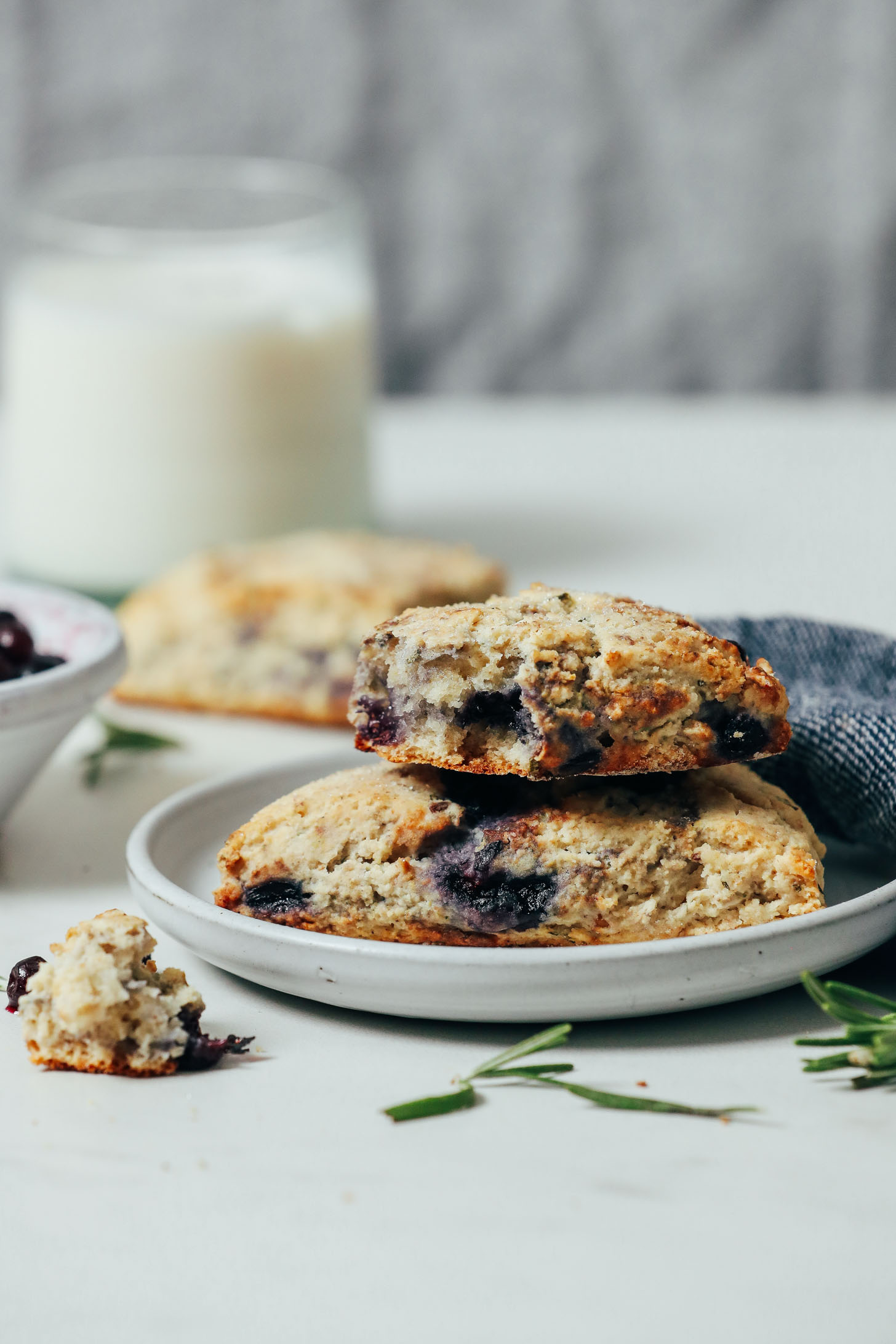 Small plate of Gluten Free Blueberry Scones beside a glass of almond milk