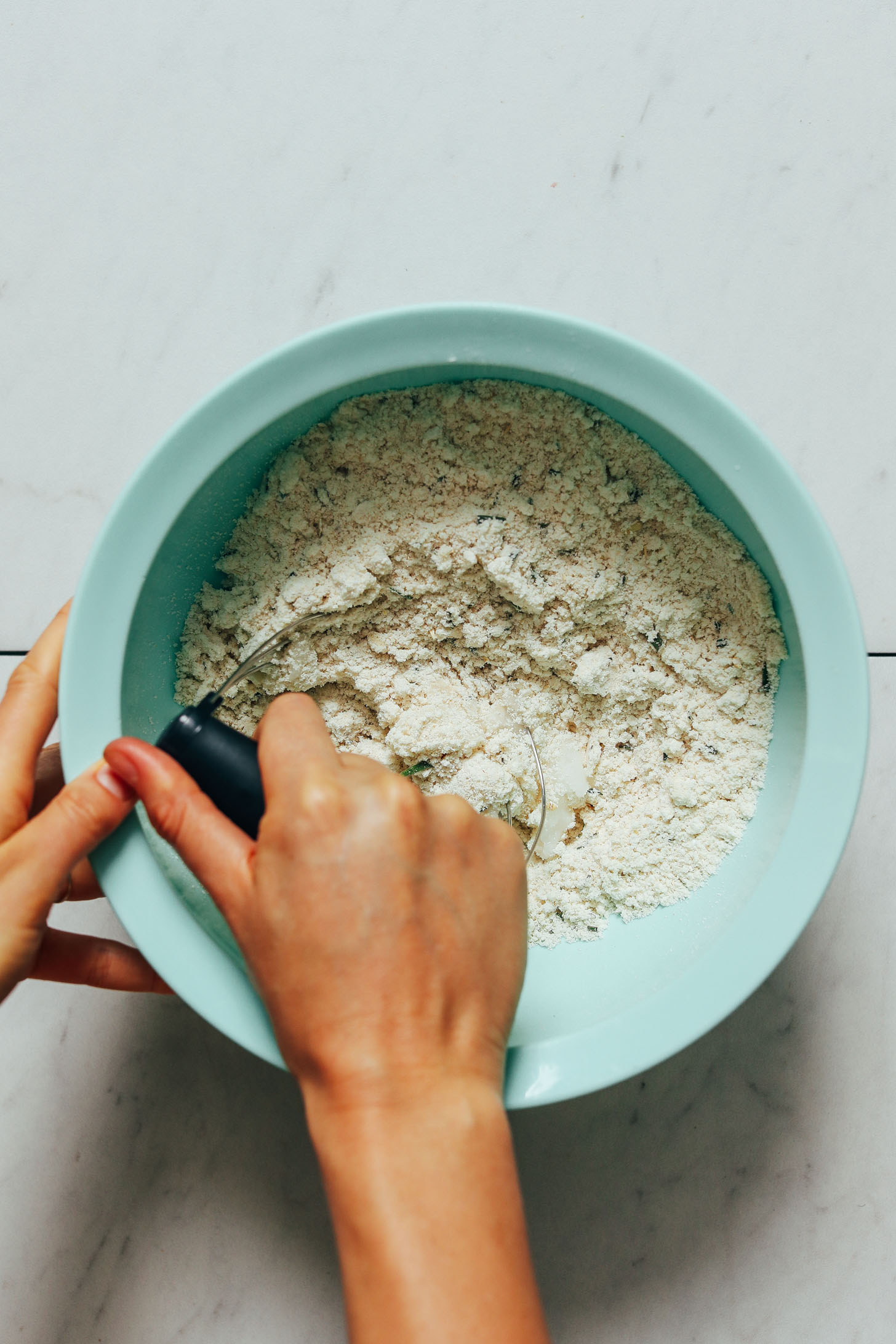 Using a pastry cutter to mix coconut oil into dry ingredients