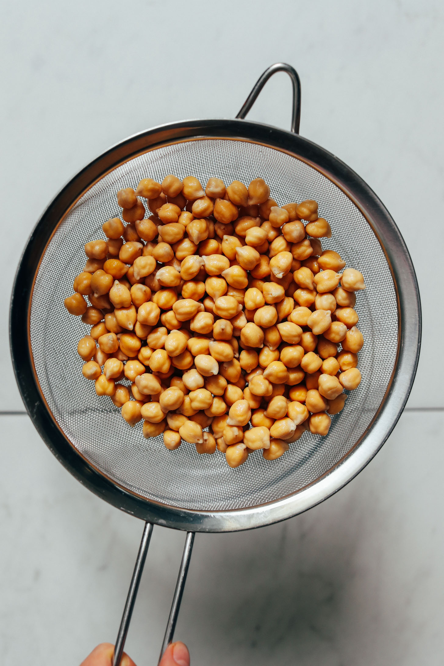 Soaked chickpeas in a fine mesh strainer