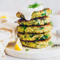 Plate of stacked Vegan Zucchini Fritters topped with dairy-free yogurt and dill