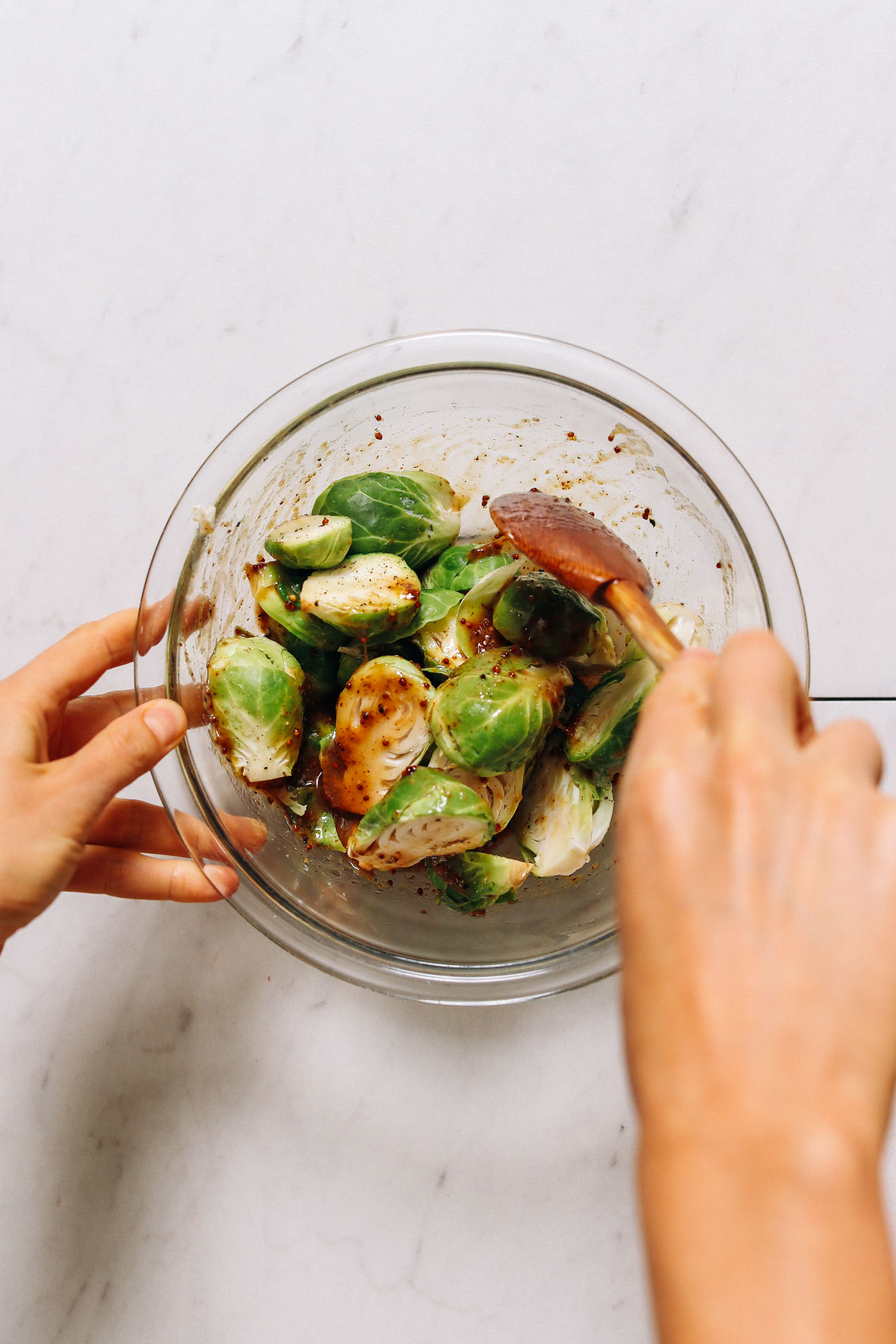 Stirring halved Brussels sprouts in a honey mustard dressing