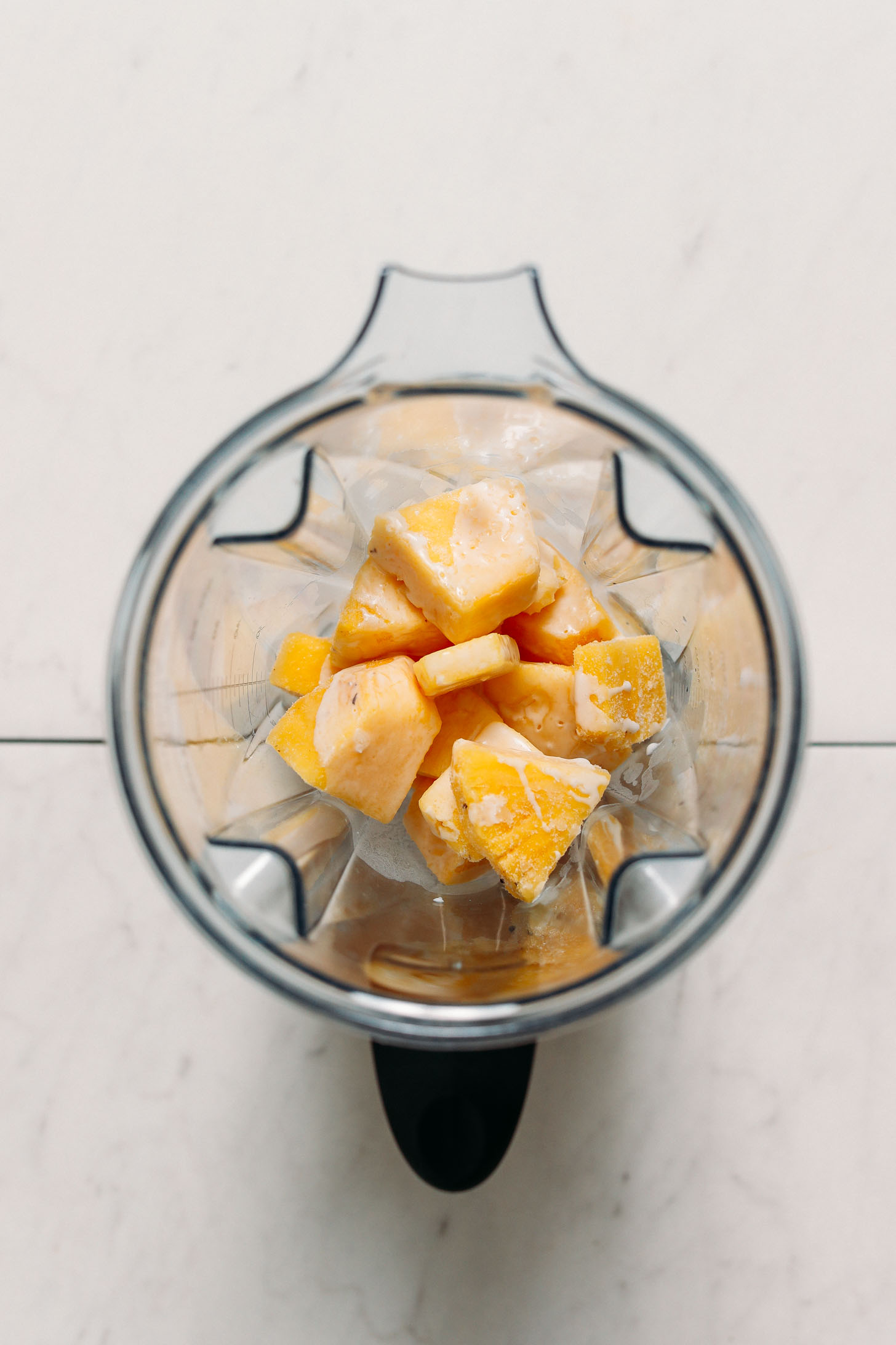 Frozen pineapple chunks and coconut milk for making a piña colada