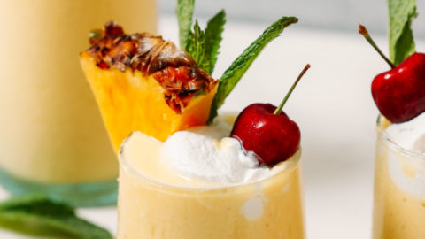 Glasses of our Piña Colada Smoothie topped with coconut whipped cream and cherries