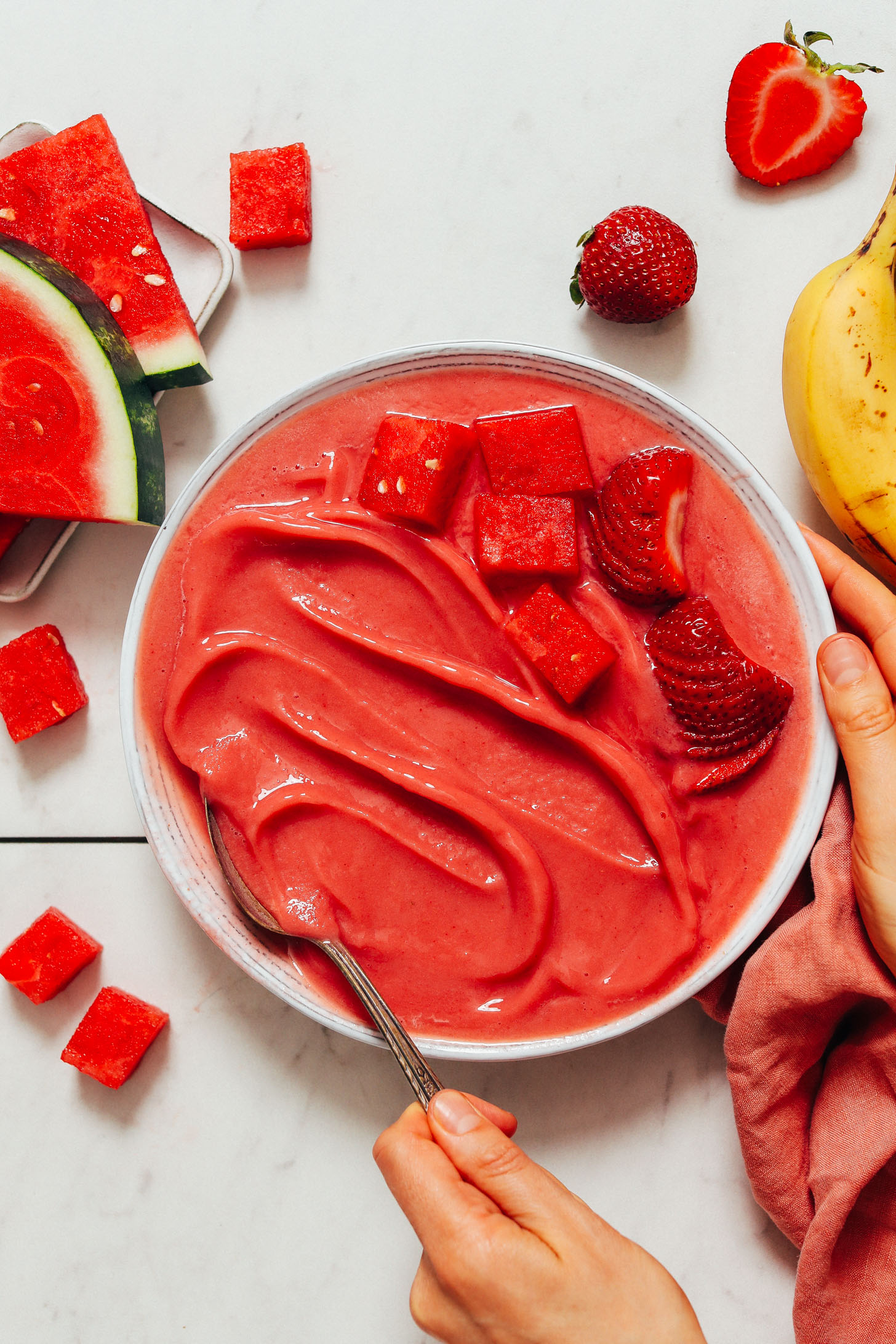 Spoon in a bowl of Watermelon Sorbet topped with fresh strawberries and watermelon chunks